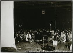 作品画像:金沢村の集会所で催された活動写真には金沢信販組合員たちが集まっての鑑賞会