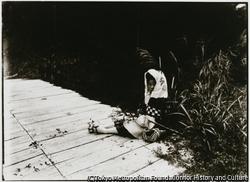 作品画像:愛らしい少女が、麦わら帽子と履き替えワラジを持って道端の野花を摘んでいた