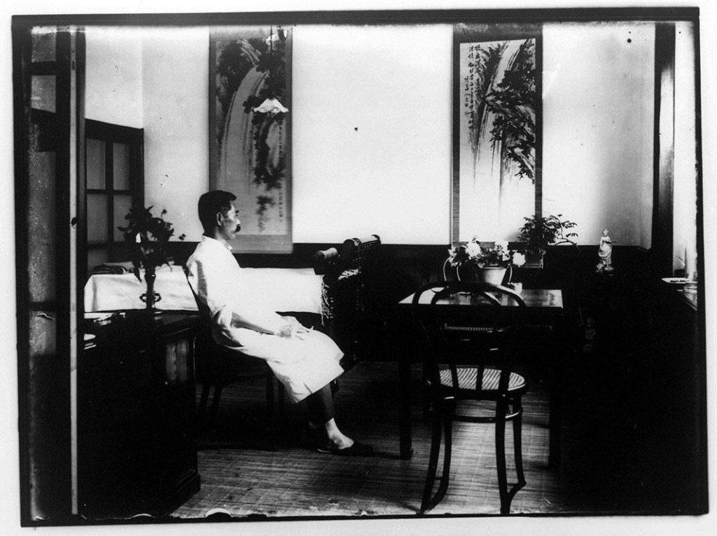 作品画像:掛軸といすに座る男性