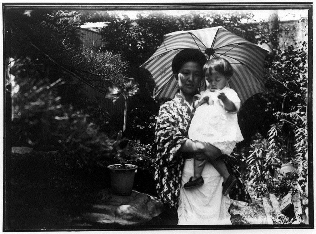 日傘をさして幼児を抱く女性