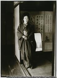 作品画像:立て縞柄模様の着物姿でポーズをつくる芸者。彼女の部屋には大きな鏡台がある