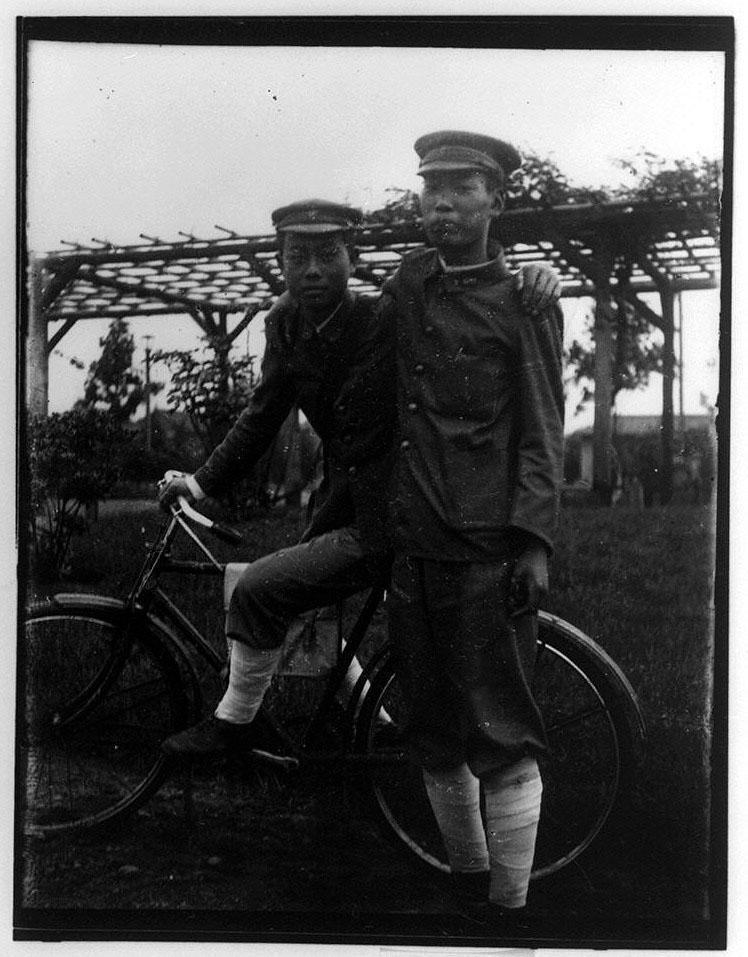 作品画像:自転車上の少年と直立する少年