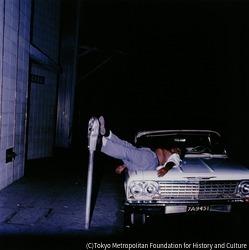 作品画像:酔いつぶれてパーキングメーターに足をのせ、車のボンネットで眠る人