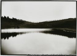 作品画像:放牧地タダラ峰の道路整備一行が山小屋へ向かう姿が、ドンデン池の水面に映る