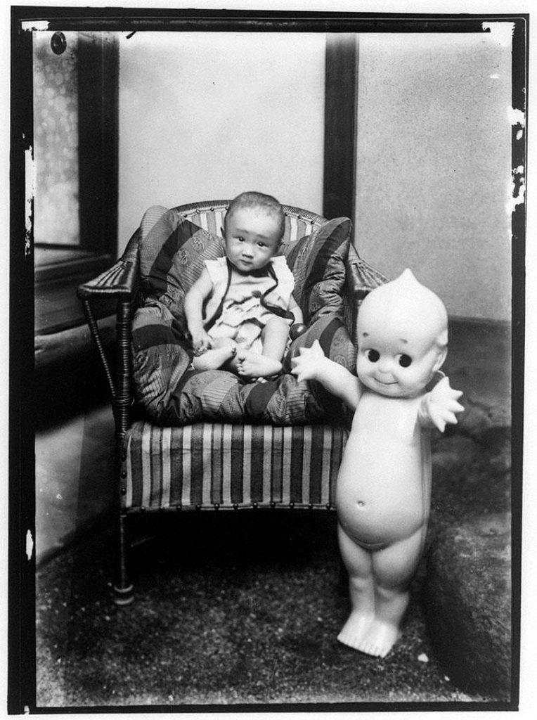 椅子に座る幼児と大きなキューピー人形