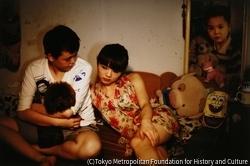 作品画像:幼少時の写真の前でのT-boyミンとシーシー、重慶
