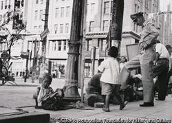 作品画像:わが子を電柱に縛り仕事する靴みがき