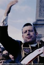 作品画像:北アイルランドの議会庁舎(ストーモント)で支持者に手を振る英国議会議員で牧師のイアン・ペイズリー。胸に「Apprentice Boys of Derry」