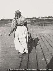 作品画像:かごを持つ女の後ろ姿、ヴェステント小菜園を背景に