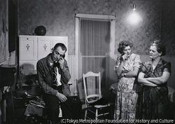 作品画像:牧師に老人の危篤状態を電話で伝えるセリアーニ、傍らで小声で話す女たち、コロラド州クレムリング 1948年