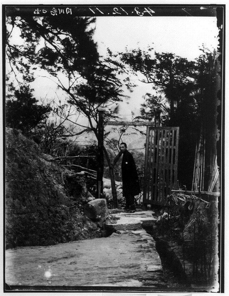 作品画像:門で振り向く男性