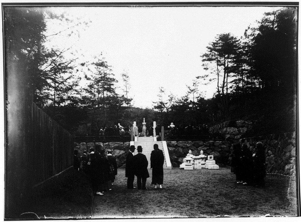 作品画像:墓の前の僧侶と男性